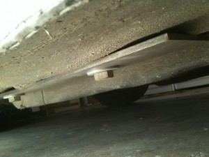 View of outboard backing plate under car